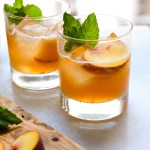 two peach bourbon smash cocktails on the counter