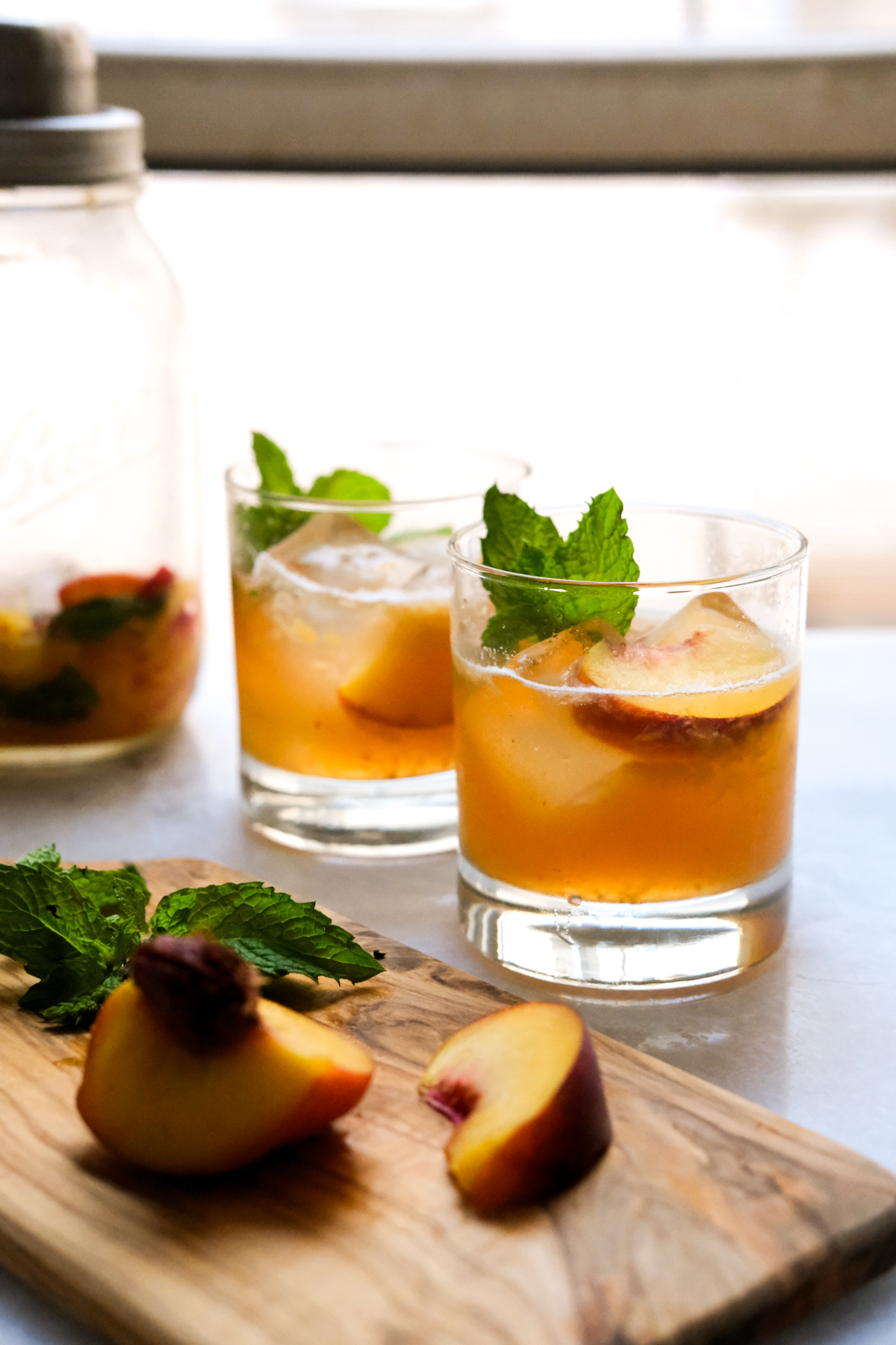 peach bourbon smash with cocktail shaker and peach slices
