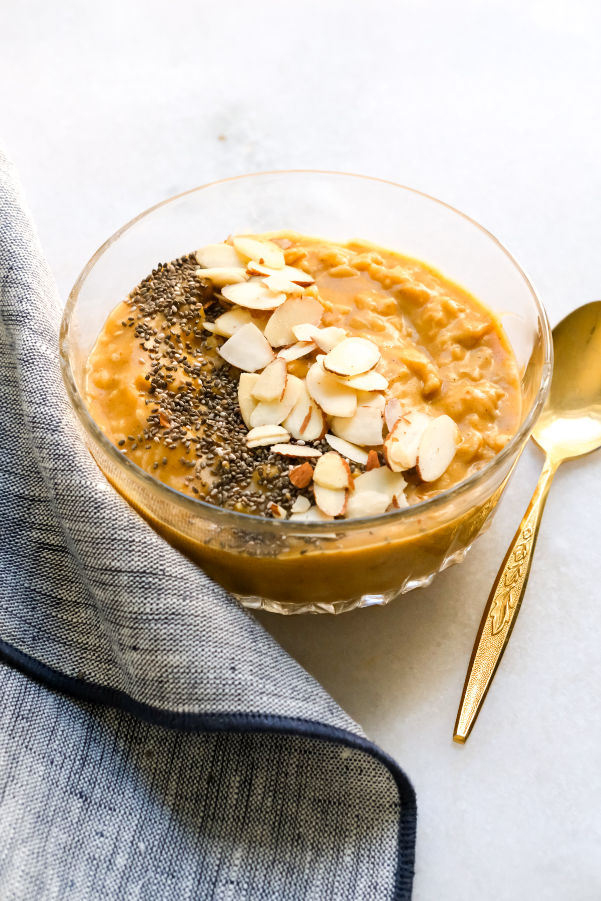 pumpkin oatmeal in a bowl with sliced almonds and chia seeds