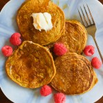pumpkin pancakes on a plate with raspberries