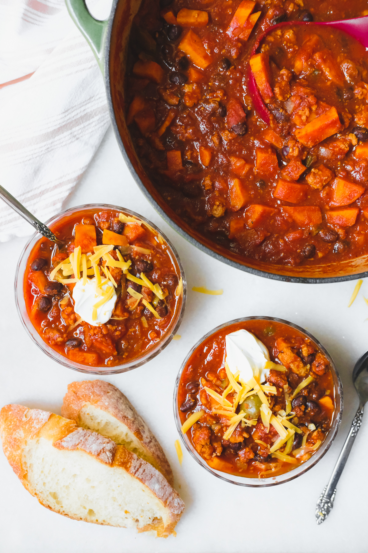 scooping bowls of sweet potato turkey chili with sour cream and cheese on top