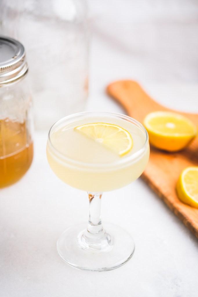 honey lemon gimlet cocktail with lemon wedge