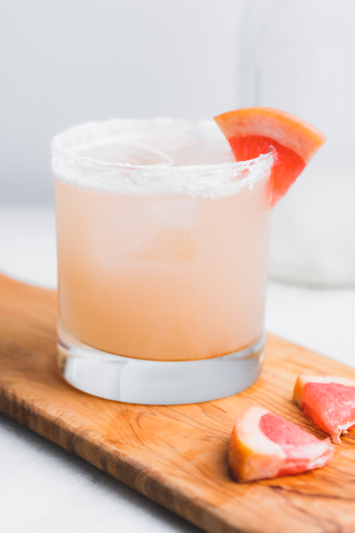 mezcal paloma cocktail on a board with grapefruit wedges and a salt rim