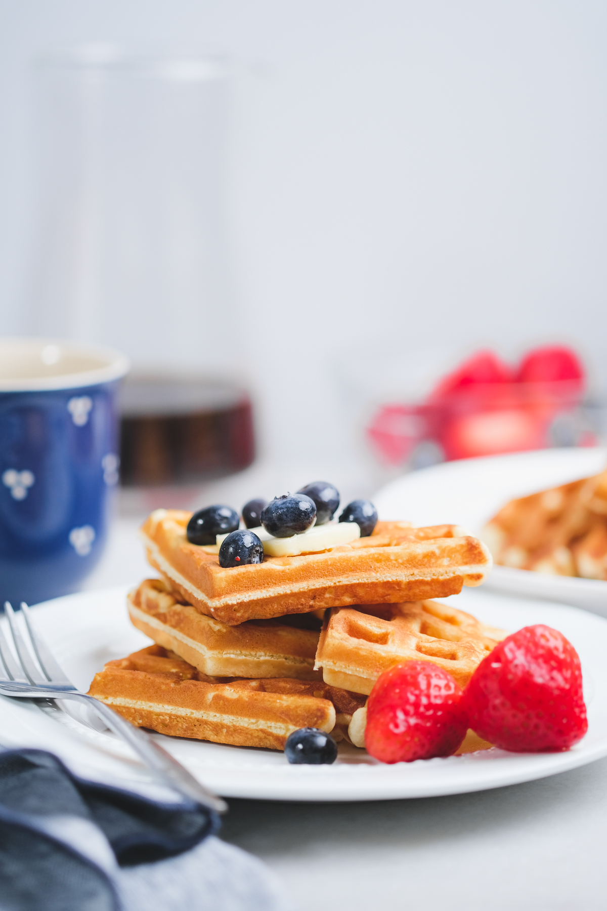 old fashioned waffles stacked on a plate with berries