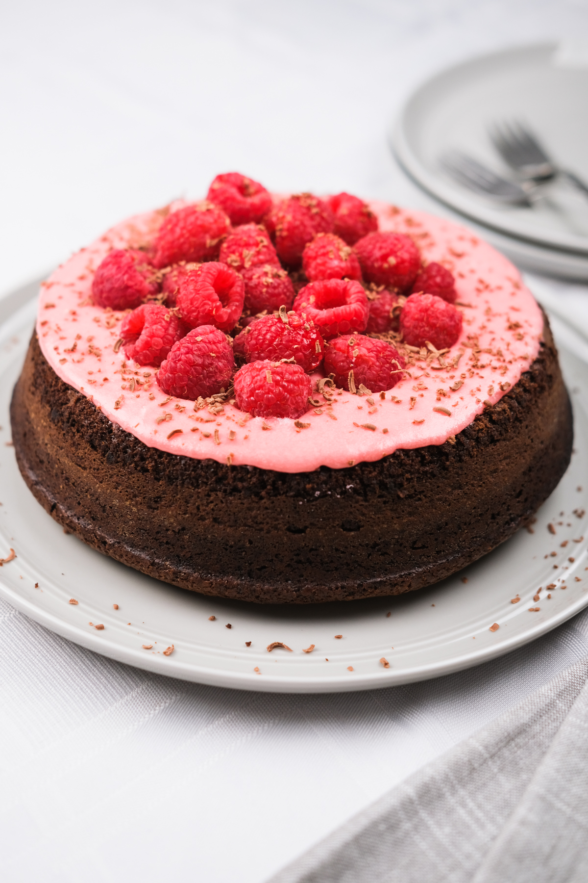 single layer chocolate cake with pink raspberry frosting and fresh berries