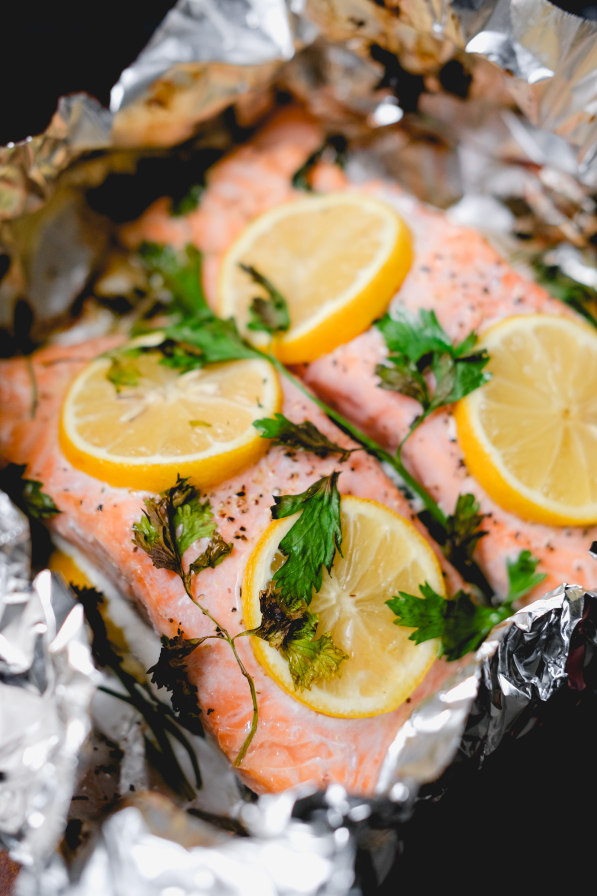 baked salmon with lemon slices and parsley in foil