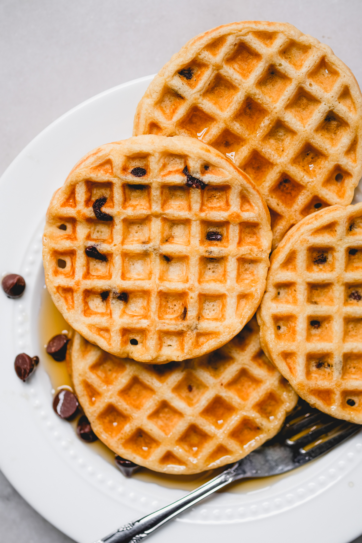 mini chocolate chip oat waffles spread out on a plate with syrup