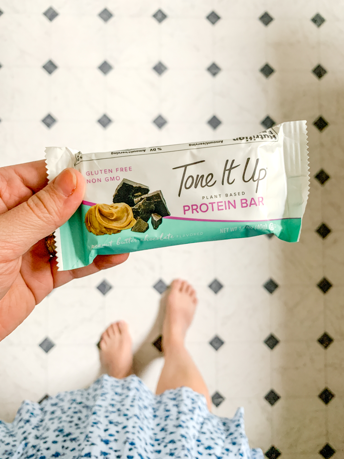 holding a tone it up chocolate peanut butter protein bar