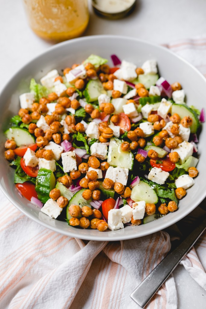 roasted chickpea greek salad in a grey bowl with dressing container on the side