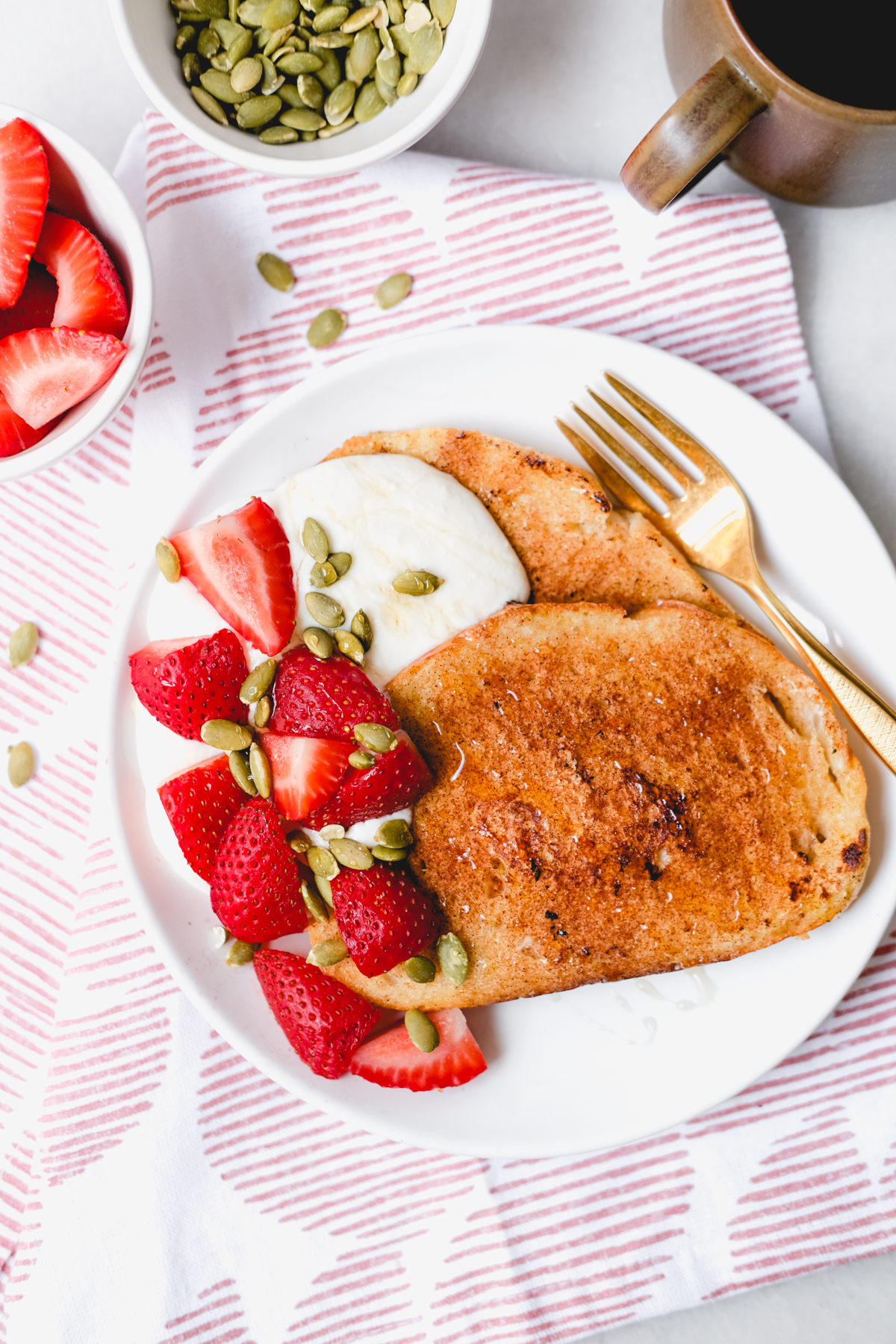 slices of french toast with honey whipped ricotta strawberries and pumpkin seeds