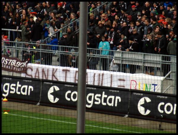 Transparent vor der Gegengerade: St. Pauli = Bunt, wobei das bunt in verschiedenen Farben geschrieben ist.