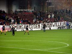 """Transparent mit der Aufschrift """"Gemeinsam gegen Terminwillkür"""" vor der alten Haupttribüne vom Millerntor-Stadion, November 2001"""