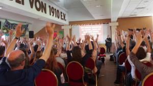 Mehrere Personen stimmen über einen Punkt ab, indem sie ihre Hand erheben