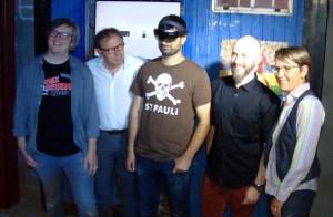 Vier Männer und eine Frau vor einer blauen Bretterwand mit FC St. Pauli-Ausstellungsstücken. Der in der Mitte stehende, blinde Mann trägt eine Mixed-Reality-Brille