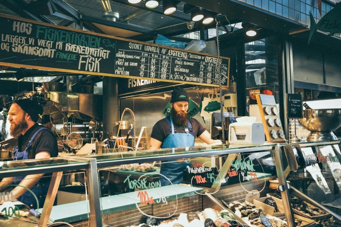 Bearded man standing behind fish counter at market