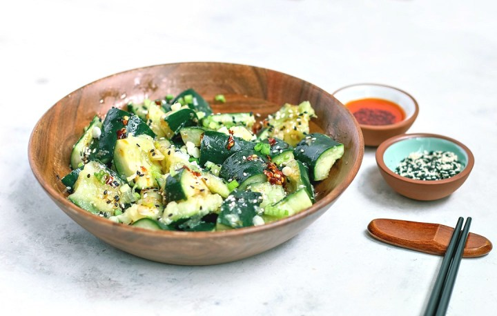 Sichuan Smashed Cucumbers with hot chili oil in a bowl.