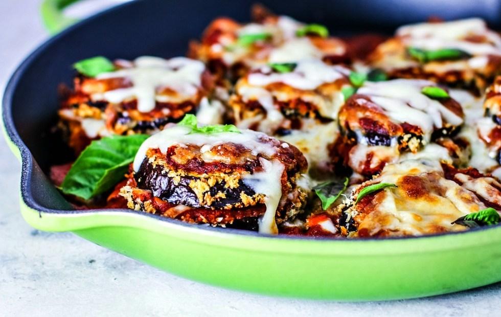 Close up of eggplant parmesan stacks in skillet.