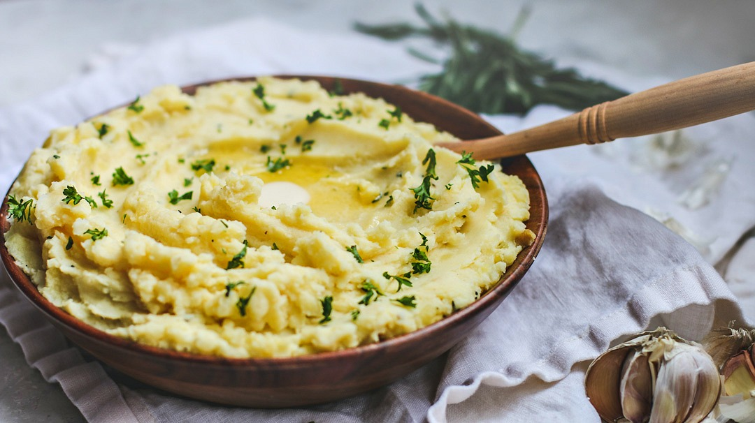 Big buttery bowl of mashed potatoes with roasted garlic and rosemary.