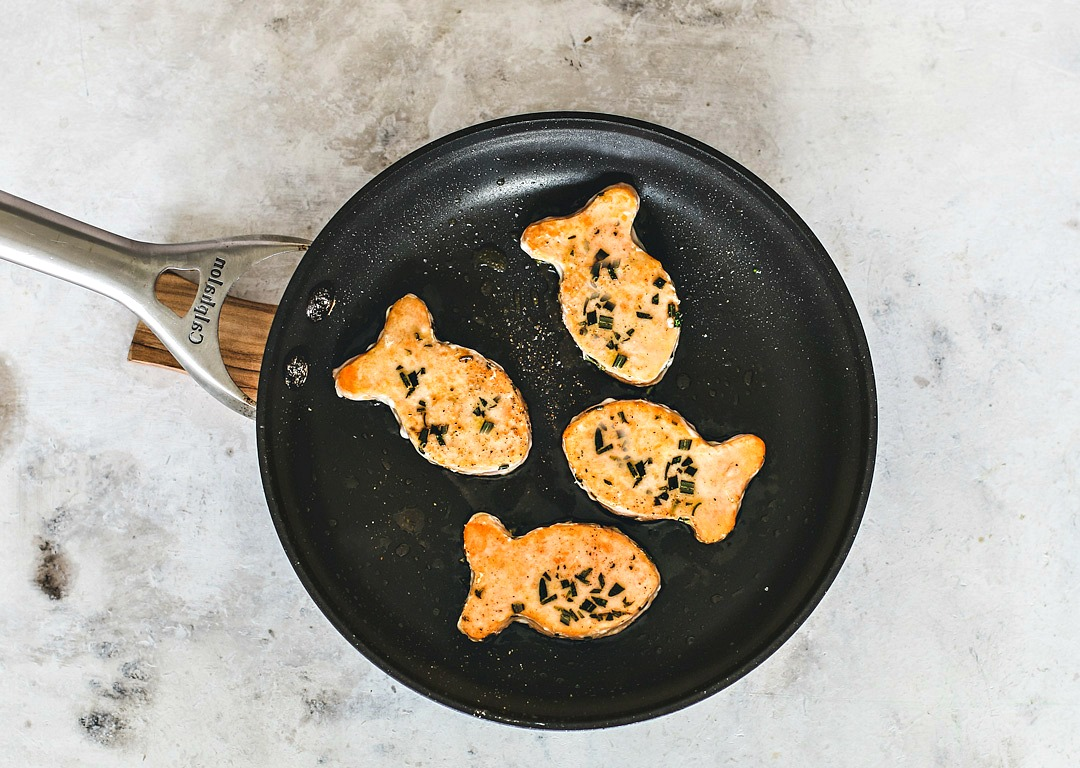 Fish-shaped salmon fillets in a frying pan.