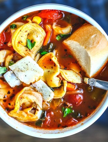Close up of bowl of vegetable and tortellini soup with bread.