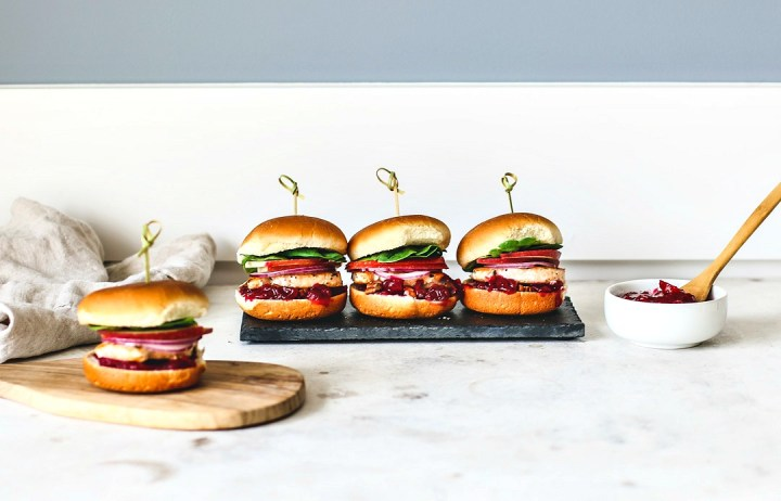 Stacked salmon sliders lined up in a row.
