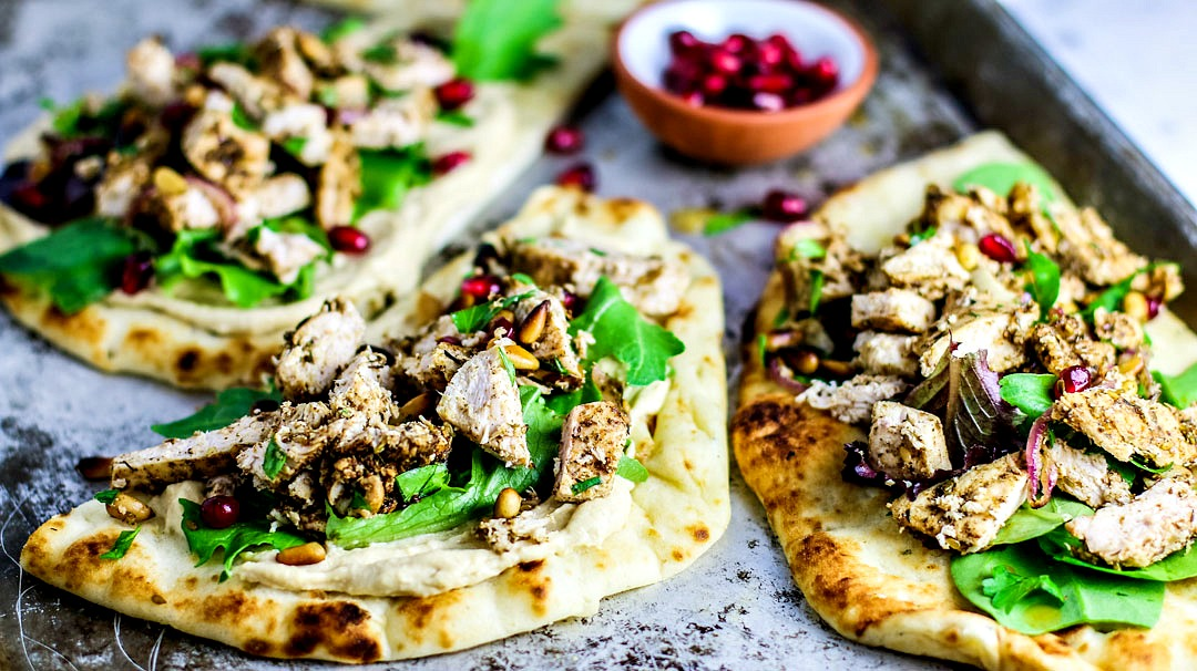 Naan breads topped with hummus, chicken, and greens.