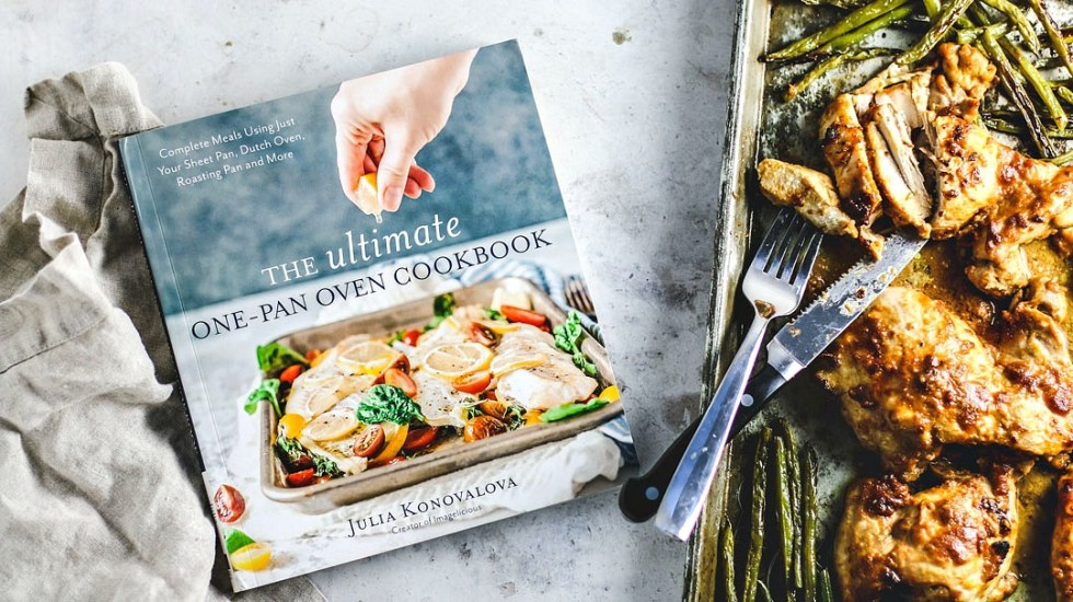 Cookbook next to sheet pan of chicken and green beans.