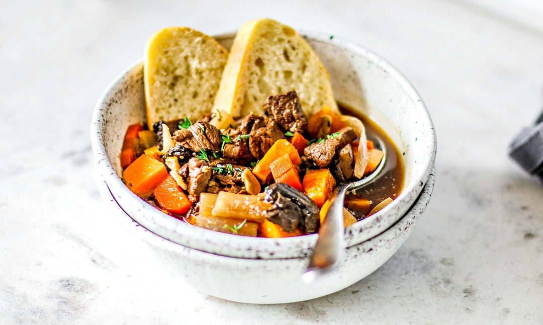 Close up of bowl of beef stew with hunks of crusty bread in it.