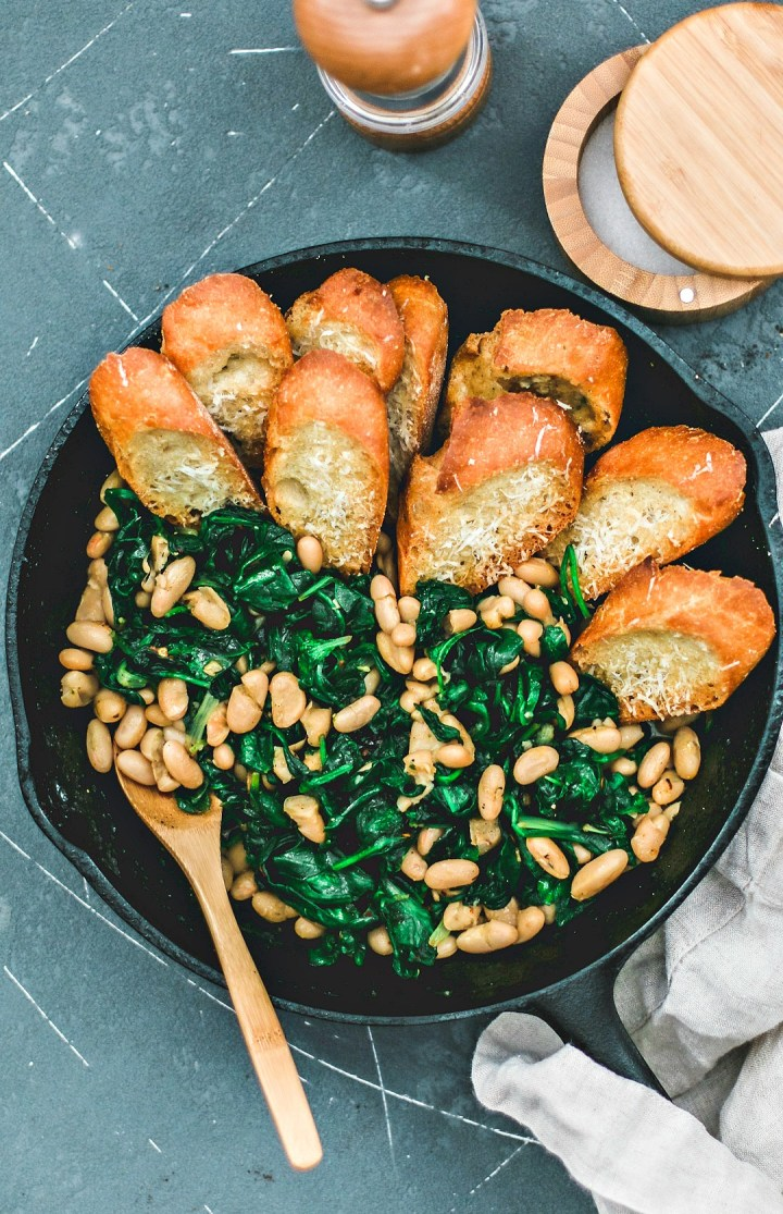 Beans and Greens in skillet lined with parmesan toasts.