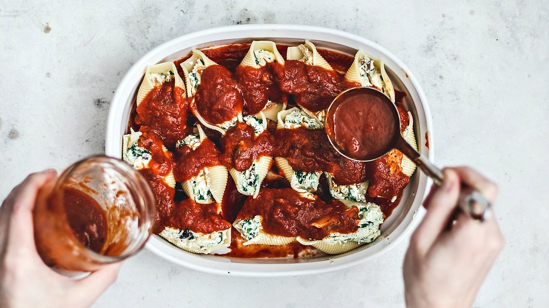 Sauce being spooned over stuffed shells in baking dish.