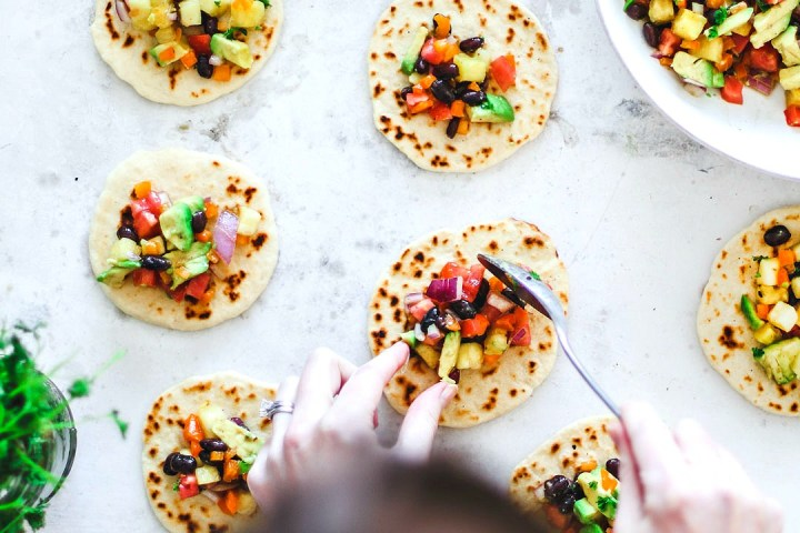 Hands topping tortillas with colorful salsa.