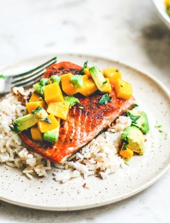 Pan-Seared Salmon on plate over rice and topped with mango and avocado salsa.