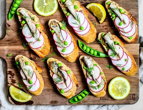 Colorful canapés topped with radishes, peas, sardines, and dill.