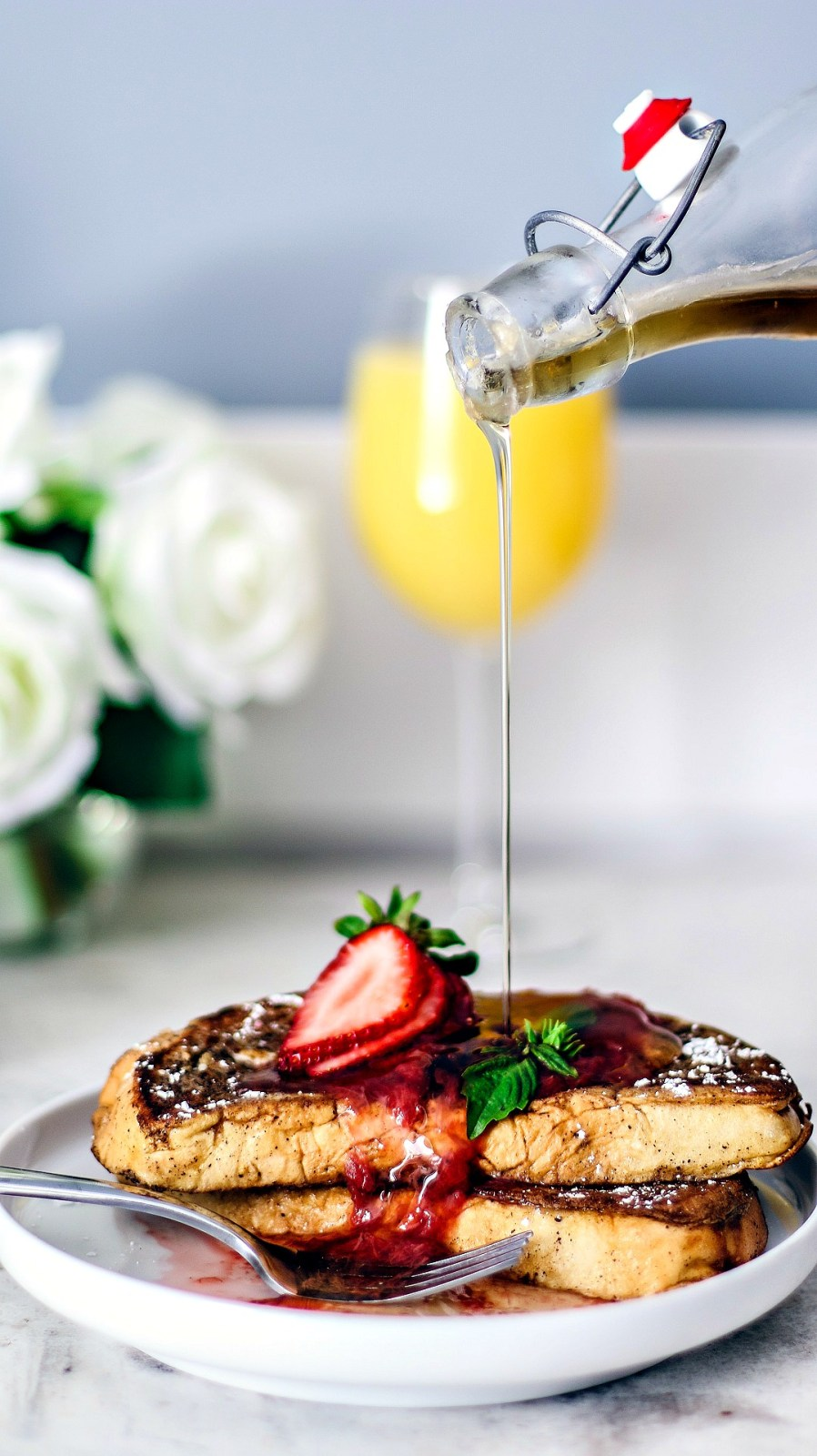 French toast getting a drizzle of maple syrup.