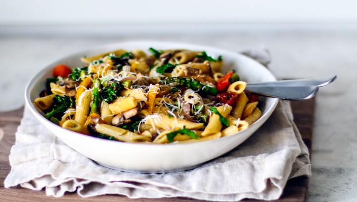 A big colorful serving bowl full of pasta and vegetables.