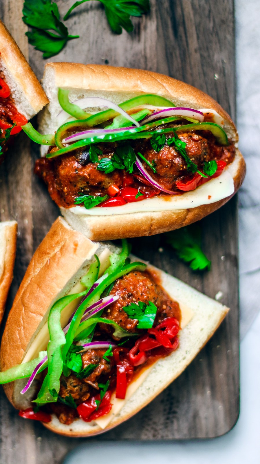 Close up of loaded meatball sub sandwiches on a serving platter.
