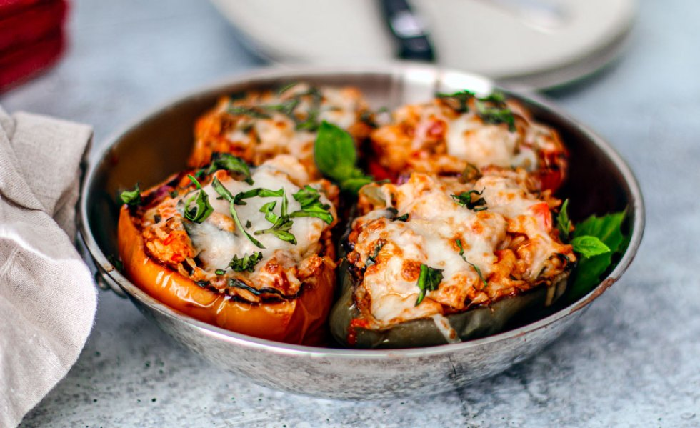 Close up of seafood stuffed peppers on table.