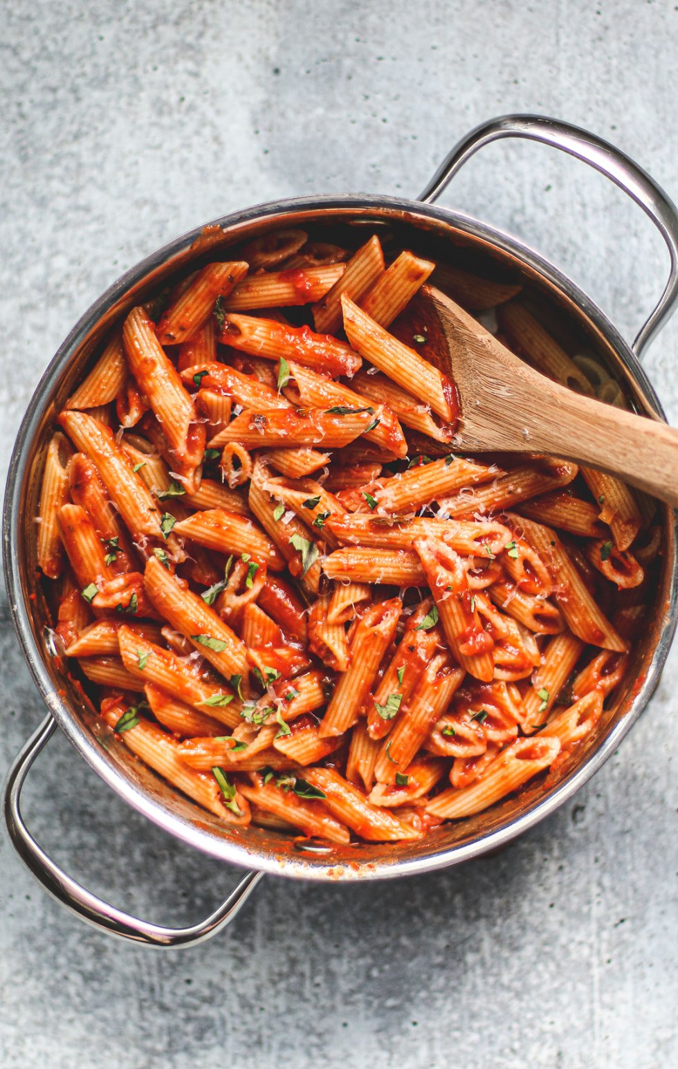 Serving pot full of penne tossed in marinara sauce and fresh herbs.