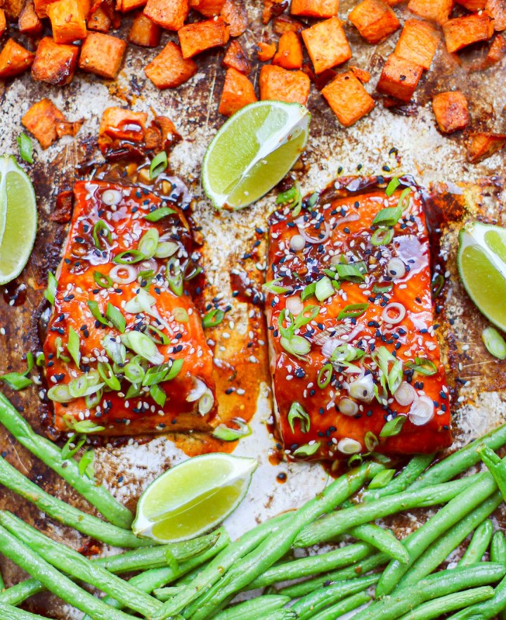 Overhead angle of two fillets of salmon on a sheet pan with veggies.