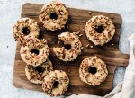 Wooden board full of maple baked donuts with pecans on top.