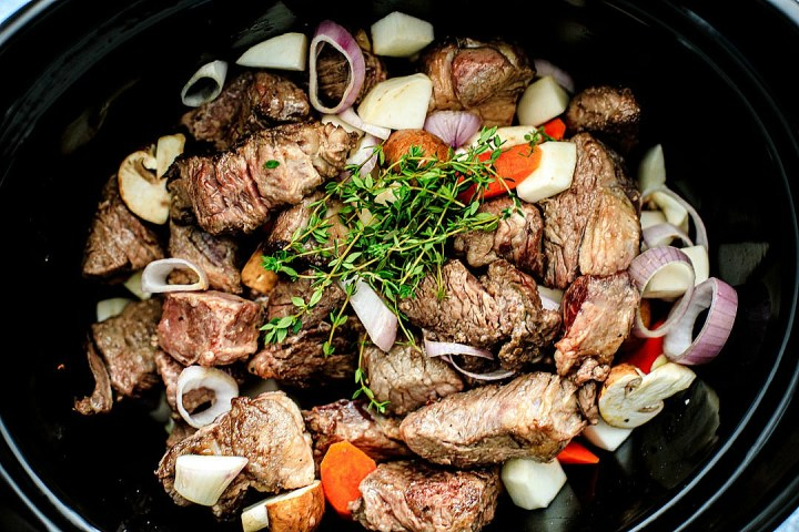 Close up of beef and veggies in slow cooker.