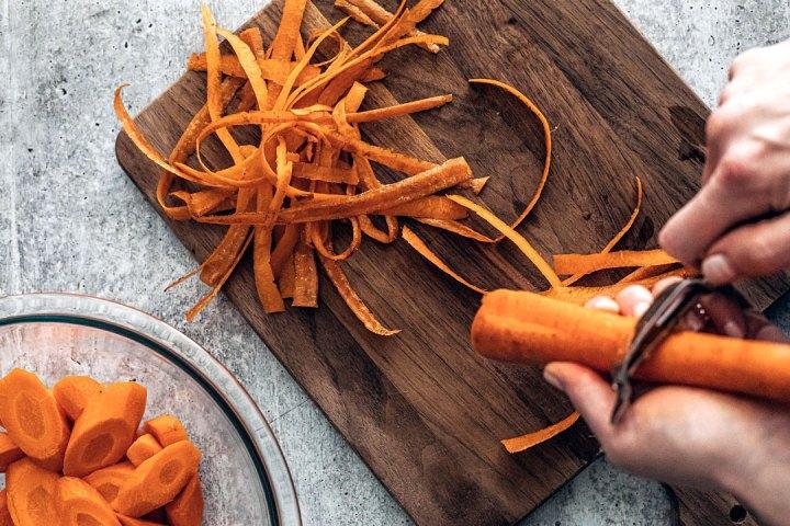 Hand peeling carrot with ribboned carrot shavings.