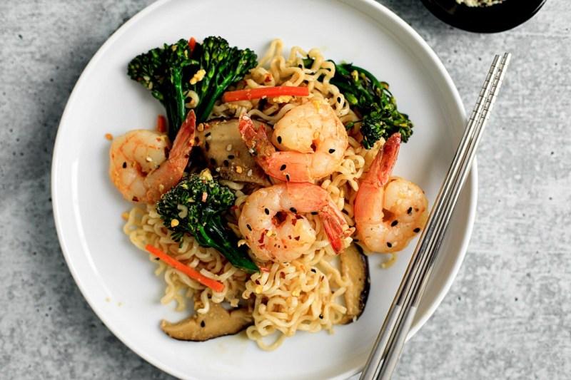 Shrimp stir-fry and Ramen noodles plated with chopsticks.