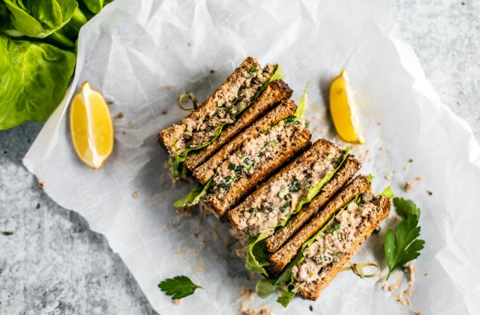 Sandwiches stacked and set down on parchment paper with lemon wedges.