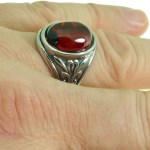 This Dragon's Eye Ring features a chunky red oval gem set on a thick decorative filigree band