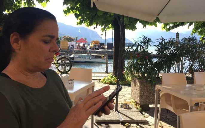 Kim getting an article assigned on her phone in Baveno, Italy