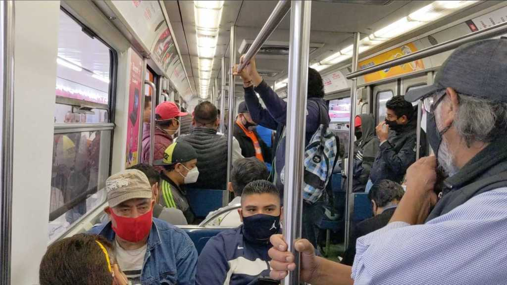 Masked passenger and open windows on the subway, Mexico City, Mexico