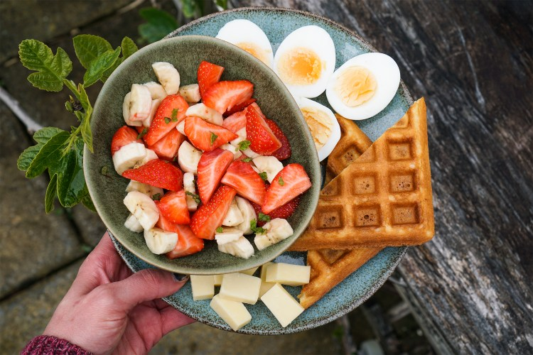 Breakfast Inspo / homemade gluten free waffles with boiled eggs, cheese and a fruit salad made with strawberries, banana, lime juice and chopped up fresh mint