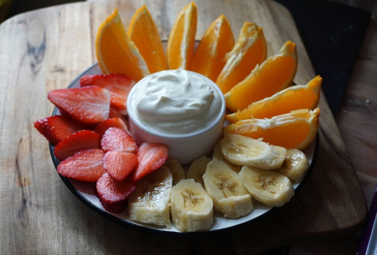 Gluten free healthy yoghurt whipped cream with strawberries, bananas and orange slices