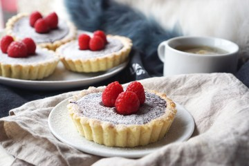 Gluten free chocolate tarts with a homemade gluten free sweet shortcrust pastry, dark chocolate and fresh raspberries on top